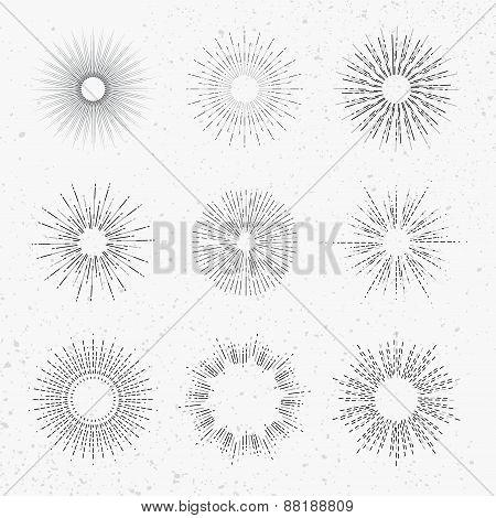 Set of different sunbursts on light background.