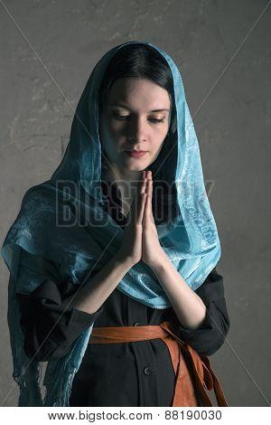 Beautiful Young Woman In A Blue  Shawl Praying