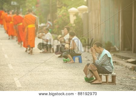 People giving alms to buddhist monks on the street, Laos