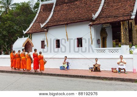 Buddhist monks collecting alms from people on the street of Luang Prabang, Laos