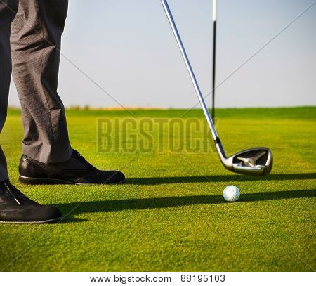 Male Golfer Putting, Focus On Golf Ball