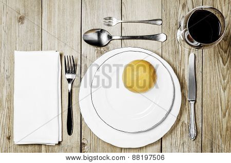 Plates with an orange, cutlery set, a napkin dining room and a wine glass on a wooden background