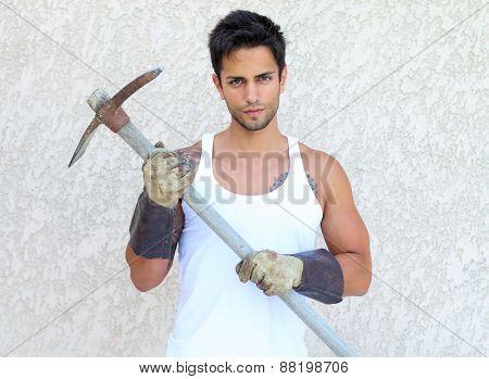 handsome gardener holding a pickaxe