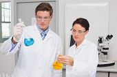image of beaker  - Scientists looking attentively at beakers in laboratory - JPG