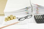 stock photo of spectacles  - Brown pencil and gold coins with spectacles and calculator have pile of paperwork as background - JPG