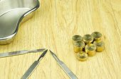 picture of scalpel  - Silver scalpel and pile of gold coins with emesis basin on wood background - JPG