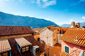 stock photo of red roof  - Top view with tiled red roofs and mountains in Kotor old city in Montenegro - JPG