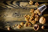 picture of walnut  - Walnut kernels and whole walnuts on wooden table - JPG