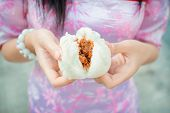foto of steam  - Chinese girl in cheongsam is tearing steamed stuff bun - JPG