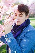 stock photo of hay fever  - woman smelling at almond tree - JPG