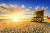 stock photo of lifeguard  - Miami South Beach sunrise with lifeguard tower and coastline with colorful cloud and blue sky - JPG