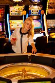 pic of roulette table  - Young blond woman playing roulette in casino and winning - JPG
