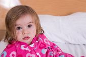 image of pyjama  - Cute young girl with tousled hair wearing pink pyjamas just awoken from her sleep giving the camera a wide eyed bemused stare - JPG