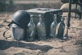 stock photo of ammo  - Old soldier helmet with ammo box and empty bottles - JPG