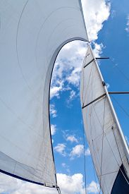 stock photo of sailing vessels  - Sails filled with wind against the sky with clouds - JPG