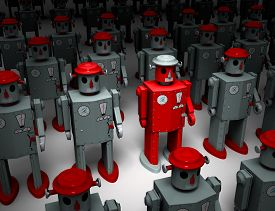 stock photo of 1950s style  - A narrow light reveals a red 1950s style tin toy robot standing out in rows of similar gray robots - JPG