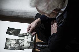 stock photo of depressed  - Senior depressed man looking at old photos - JPG