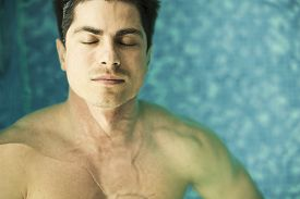 picture of floating  - Young man floating in the swimming pool - JPG