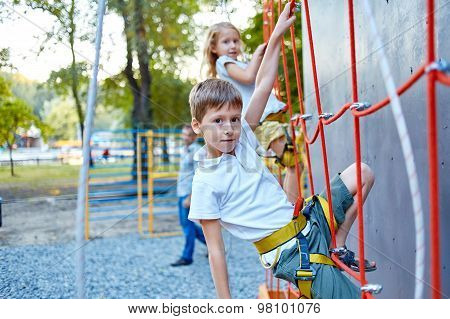 Little boy and girl  in  rock climbing gym
