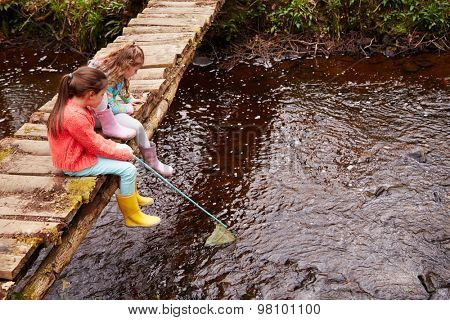 Two Girls Sitting On Bridge Fishing In Stream With Net