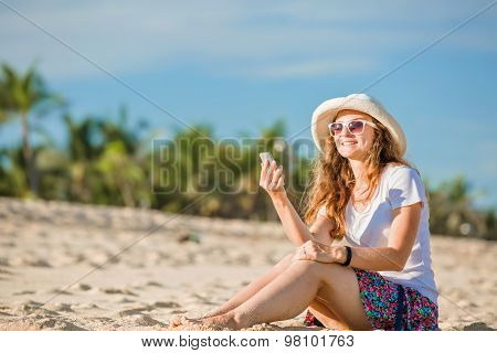 Beautiful young woman on the beach at sunny day with mobile phone