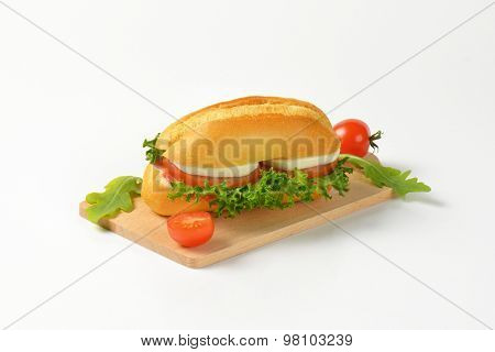 bun sandwich with mozzarella cheese and fresh vegetables on wooden cutting board