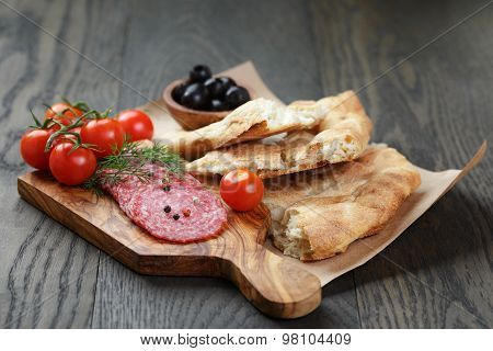 pita bread salami and vegetables on table