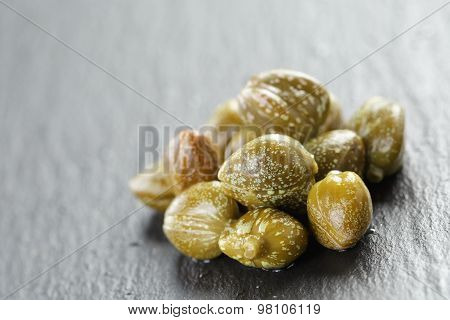 marinated capers in olive bowl on slate board