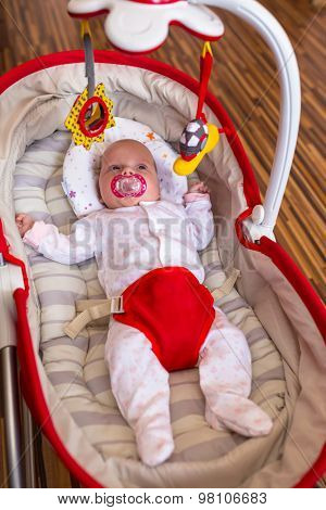 Baby girl lying down in the cradle with toys