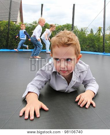 Funny kids playing and jumping on a outdoor trampoline.