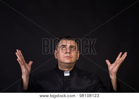 The priest. An actor dressed as a Catholic priest.