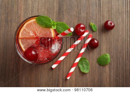 Glass of cherry juice on wooden table, top view