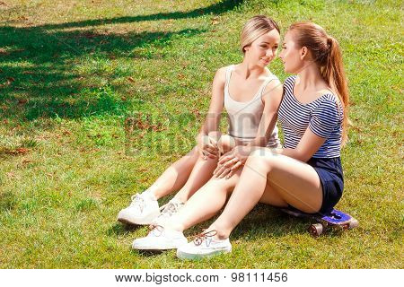 Two lesbians sitting on grass in park