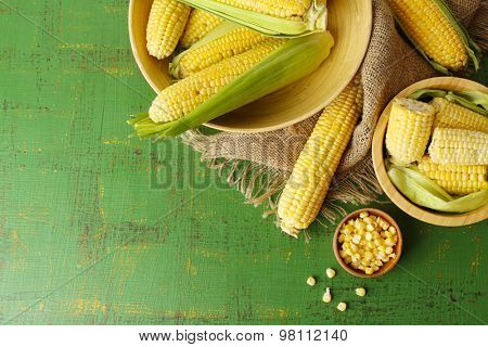 Fresh corn on cobs on green wooden table, top view