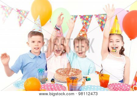 Happy children posing with birthday cake