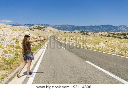 Young woman hitchhiking along empty road