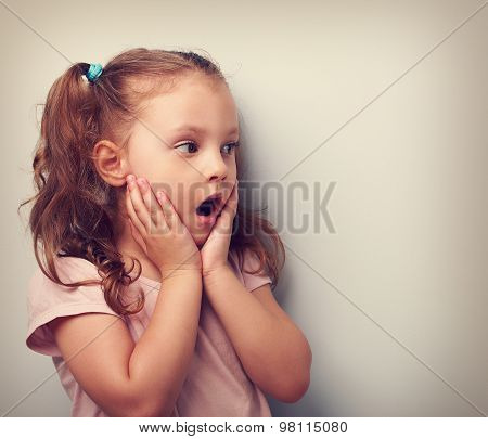 Surprising Kid Girl With Opened Mouth And Hand Near Face Looking On. Toned Portrait