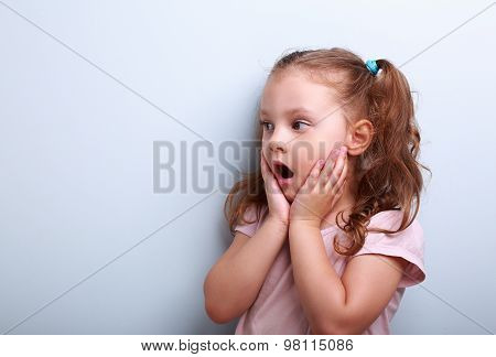 Surprising Kid Girl With Opened Mouth And Hand Near Face Looking On