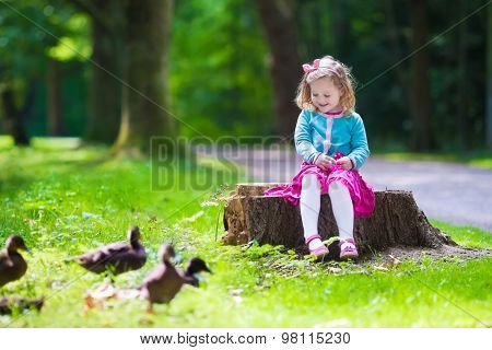 Little Girl Feeding Ducks In A Park