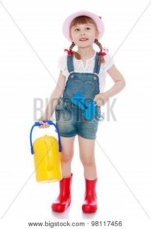 Little girl watering a garden