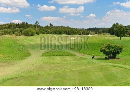 Green Golf Course And Blue Cloudy Sky. Field With Trees Landscape
