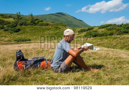 Man tourist in mountain read the map.