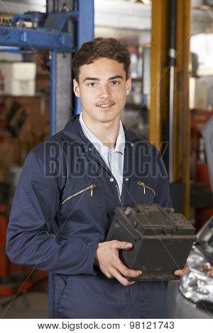 Apprentice Mechanic Holding Car Battery In Auto Repair Shop