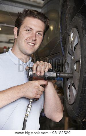 Mechanic In Garage Using Air Hammer On Car Wheel