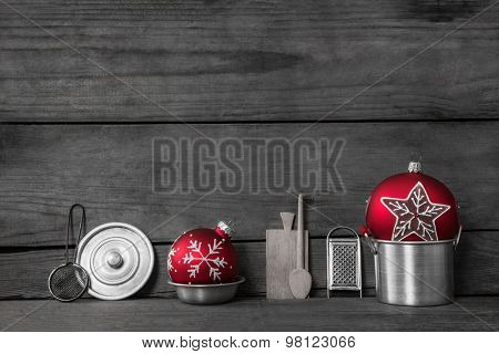 Christmas dinner. Wooden grey background with decoration of old silver tin miniatures for the kitchen and red xmas balls.