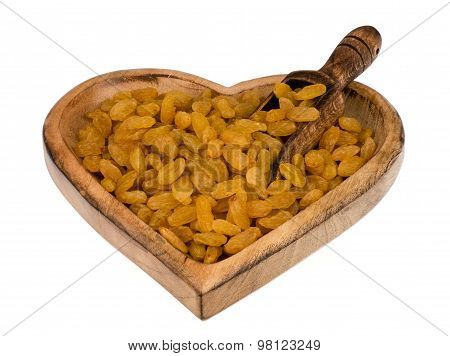 Yellow raisins in the wooden bowl isolated.