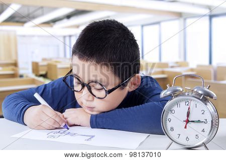 Child Drawing In Class With A Clock On Desk