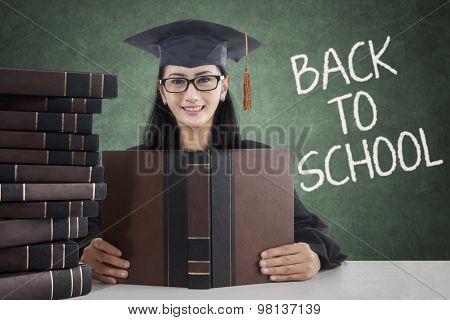 College Student With Mortarboard Holding Book