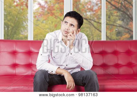 Confused Man Sitting On Couch