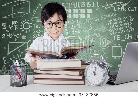 Kid Reading Book With Clock On The Table